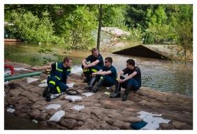 THW-Helfer sitzen auf Sandsackschneise zwischen zwei überfluteten Ortsteilen nahe Dresden, Niedersedlitz. (A team from technical emergency service sits on sandbags in conversation near Dresden, Niedersedlitz.)