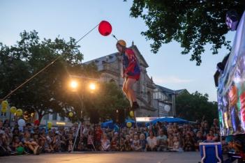 """Der Australier """"Ernest the Magnifico"""" versucht einen Luftballon mit einer an seinem Helm befestigten Gabel zum Platzen zu bringen, Grüner Markt, Bamberg.;"""