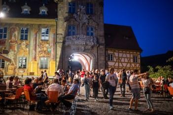 """Eine laue Sommernacht: Viele Menschen pendeln zu Fuß zwischen den vielen Bühnen von """"Bamberg zaubert"""". Wer eine Pause vom Trubel braucht, erholt sich in einem der vielen Cafés, Untere Brücke, Bamberg.;"""