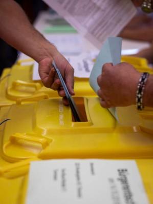 Die ausgefüllten Wahlunterlagen werden bei einem Wahlhelfer abgegeben. (The completed election documents are handed into a ballot box.)